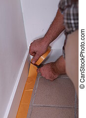 Man sticking tape to skirting board