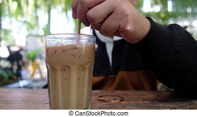 Man stirring of iced coffee mocha by straw in glass at cafe