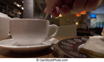 Man stirring tea in the cup a cafe. 4K close up shot