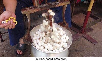 Man Stirs Silk Egg Sacks in Hot Water to Separate Trash.