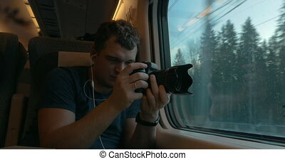 Man stocker in train listening to music and making footage -...