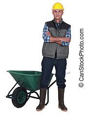 Man stood by empty wheelbarrow