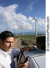 Man stood by wind farm taking readings