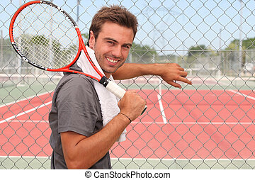 Man stood in front of tennis court holding racket over...
