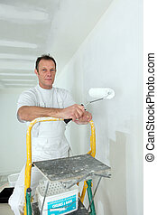 Man stood on ladder painting wall