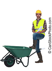 Man stood with empty wheelbarrow