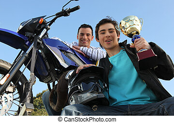 Man stood with motorbike and trophy