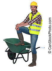 Man stood with one foot on wheelbarrow