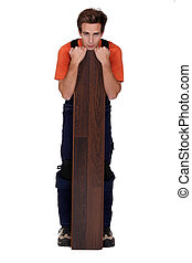 Man stood with plank of laminate flooring