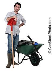 Man stood with spade and wheelbarrow