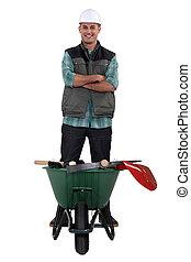 Man stood with wheelbarrow full of tools