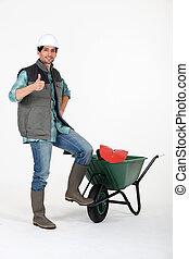 Man stood with wheelbarrow giving thumbs-up
