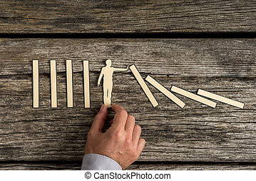 Man stopping the domino effect with a paper cutout silhouette