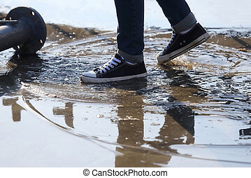 man stops with his foot in a puddle