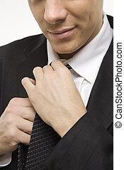 Man straightening necktie. - Close-up of Claucasian...