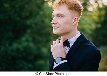 Man straightens bow-tie before the ceremony