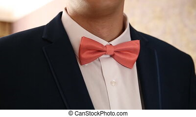 man straightens his bow tie