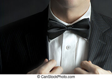 Man Straightens Tux - A close-up shot of a man straightening...