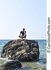 Man stranded on a rock in ocean