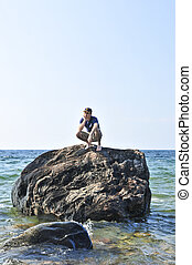 Man stranded on a rock in ocean waiting for rescue