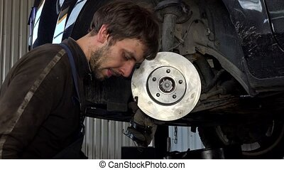 Man strengthen brake discs and pads in garage.