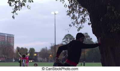 Man stretches his quads by a tree, silhouette