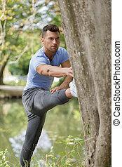 man stretching his leg on a three