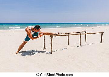 man stretching on the beach