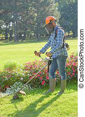 Man strimming grass