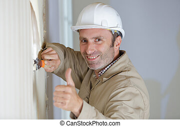 man stripping wallpaper making thumbs-up gesture