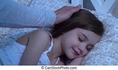 Man strokes his daughter's head, she sleeps. Close up - Man...