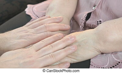 Man strokes old wrinkled woman's hands. Close up