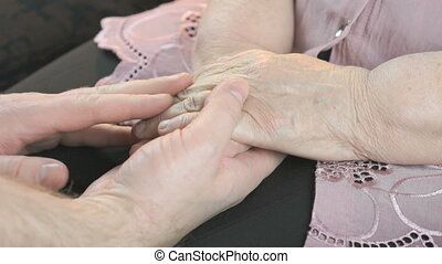 Man strokes the old woman's hands during illness - Man...