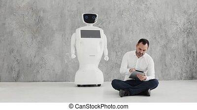 man stroking a robot. friendship with a robot. Modern...