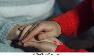 Man stroking a woman's hand, close up, caring for a loved one