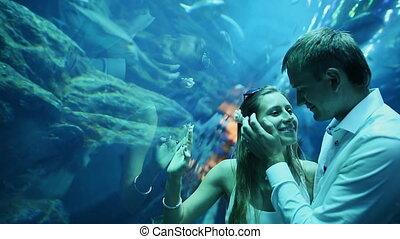 Man stroking the girl's face in underwater Aquarium Dubai Mall