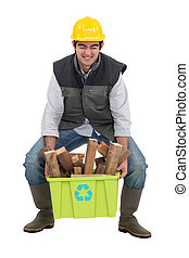 Man struggling to lift box of wood to be recycled