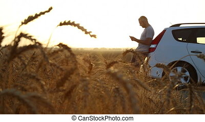 Man stuck with car in a wheat field - Shot of Man stuck with...