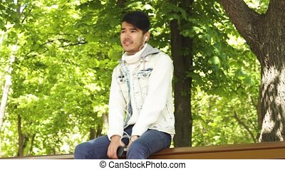 Man student listening music sitting in spring park