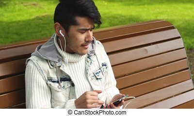 Man student listening music sitting in the park