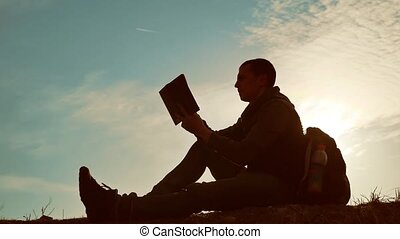 Man student reading in the park with backpack against...