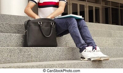 Man student with books on stairs putting his books in bag...