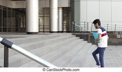 Man student with books walking up stairs of his university