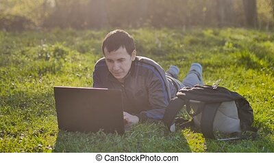 man student with laptop sitting on green grass lawn sunlight lifestyle