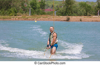 Man study wakeboarding on a blue lake