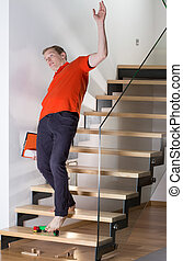 Man stumbling over child's toy on the stairs