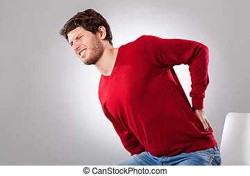 Man suffering from backache - Young man suffering from ...