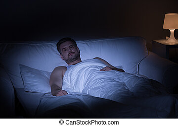 Man suffering from insomnia - View of man at night suffering...