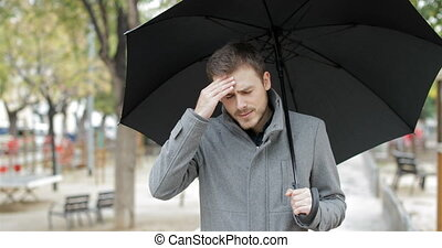 Man suffering head ache under the rain - Angry man suffering...