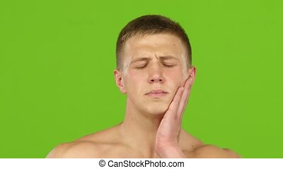 Man suffers from toothache and rubs jaw with hand. Closeup -...